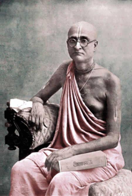 Bhaktisiddhanta sitting with book